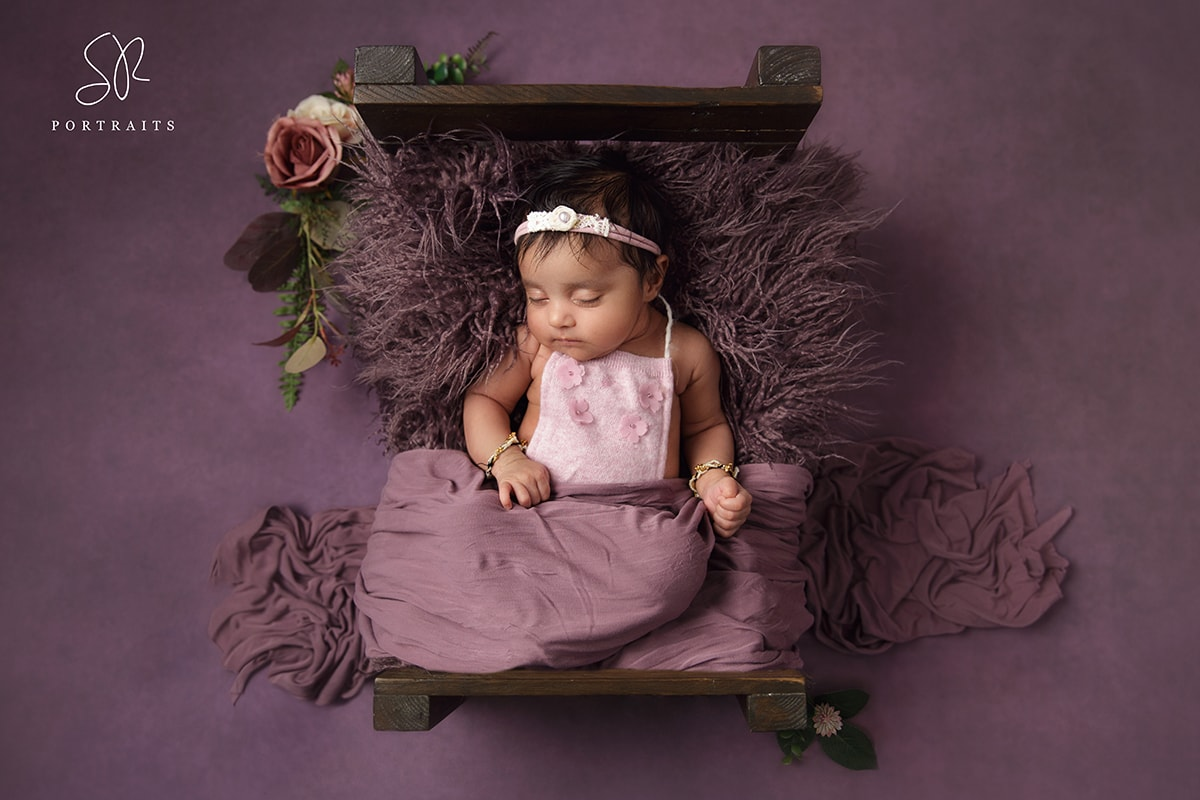 Baby girl in purple on purple background newborn photography leicestershire